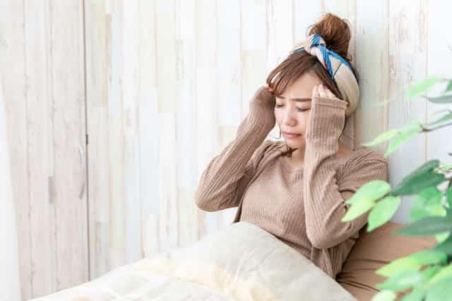 辛い頭痛で起きるのも憂鬱な女性